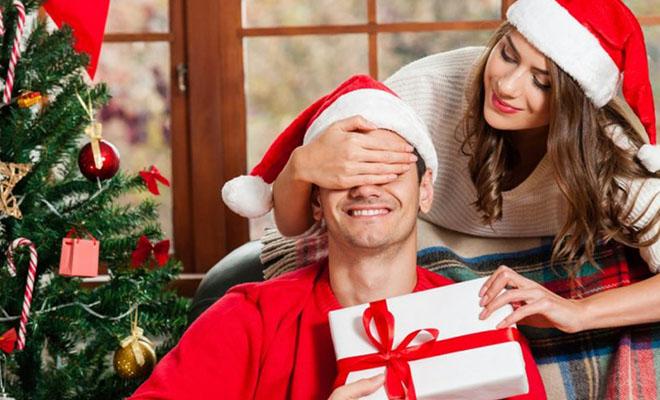 девушка дарит новогодний подарок парню