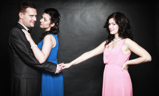 мужчина держит другую за руку за спиной жены