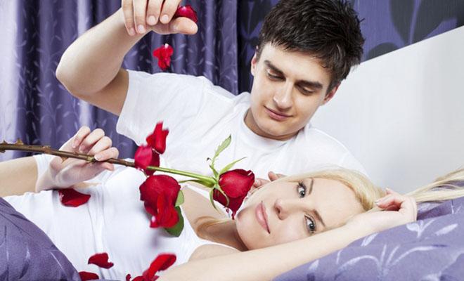 мужчина осыпает женщину лепестками роз
