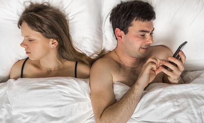 мужчина переписывается по телефону в постели с женой