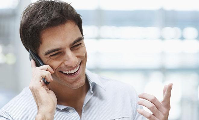 мужчина с улыбкой разговаривает по телефону