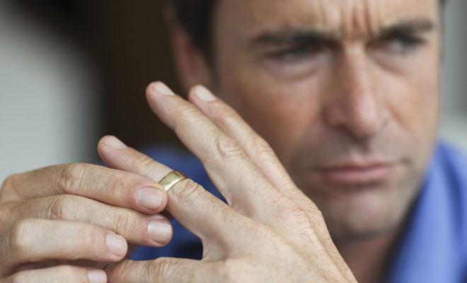 мужчина снимает обручальное кольцо