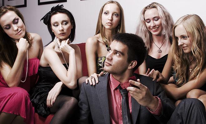 мужчина в окружении девушек