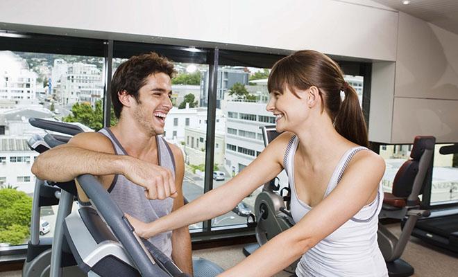 парень флиртует с девушкой в спортзале