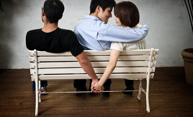 женщина держит за руку другого за спиной мужа