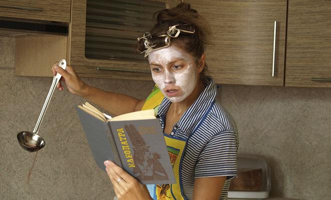 женщина в маске и бигудях готовит