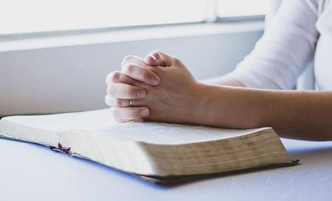 человек молится на библии