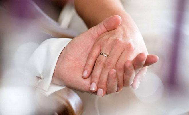 руки молодоженов с кольцом