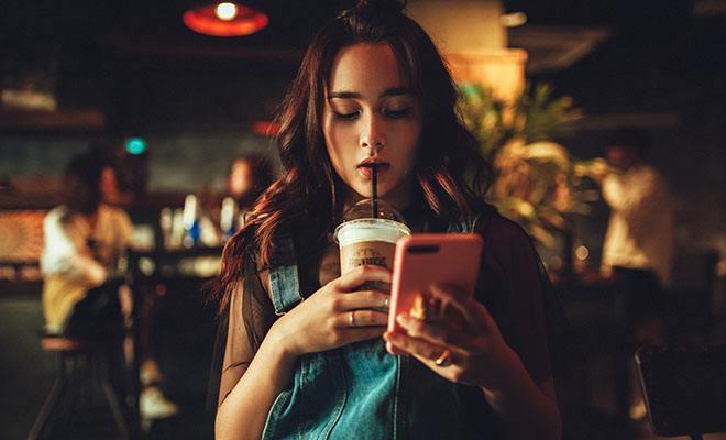 девушка пьет коктейль с телефоном в руках