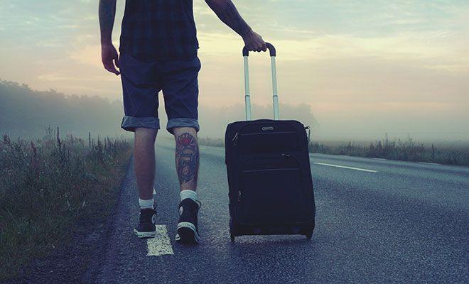 мужчина стоит на дороге с чемоданом
